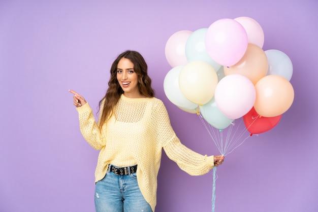 Jonge vrouw die vele ballons over geïsoleerd op purpere muur vangt die vinger aan de kant richt