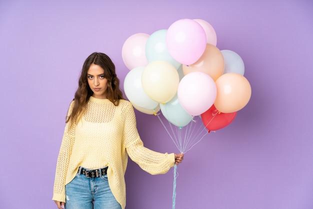 Jonge vrouw die vele ballons over geïsoleerd op purpere muur vangt die wapens gekruist houden