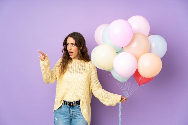 Jonge vrouw die vele ballons over geïsoleerd op purpere muur vangt die weg richten