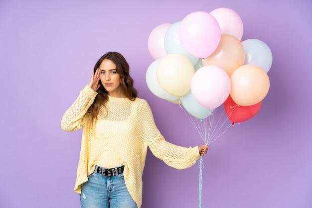 Jonge vrouw die vele ballons over geïsoleerd op purpere muur vangt ongelukkig en gefrustreerd met iets. negatieve gezichtsuitdrukking
