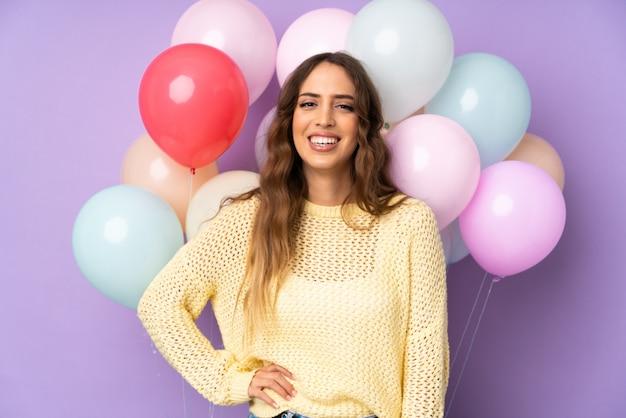 Jonge vrouw die vele ballons over geïsoleerd op purpere muur vangt