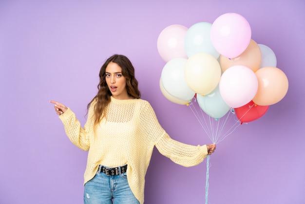 Jonge vrouw die vele ballons over geïsoleerd op purpere muur verrast verrast en vinger aan de kant richt