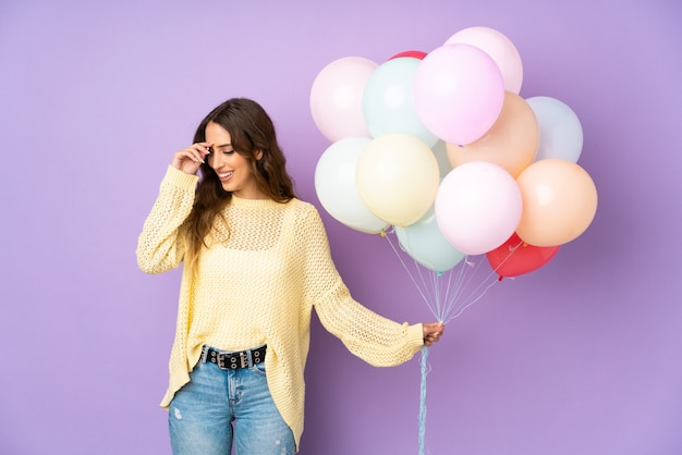 Jonge vrouw die vele ballons over geïsoleerdt bij het purpere muur lachen vangt