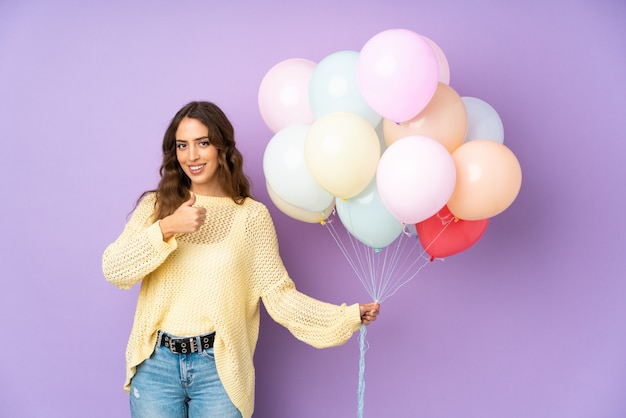 Jonge vrouw die vele ballons over op het purpere muur geven duimen op gebaar vangen