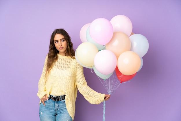 Jonge vrouw die vele ballons over op purpere muur overhaalt die een idee denkt