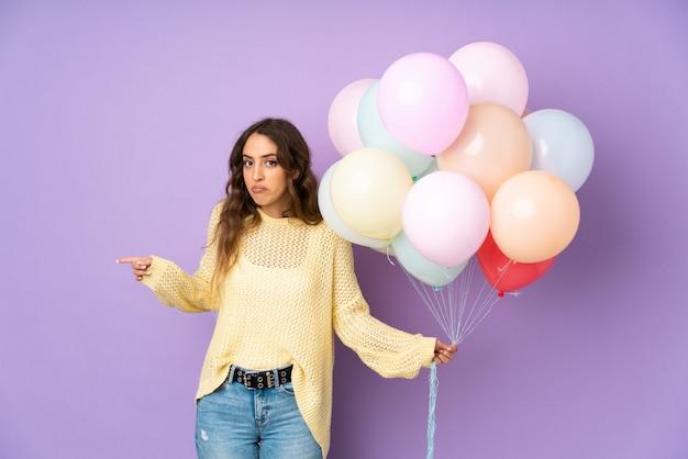 Jonge vrouw die vele ballons over op purpere muur overhaalt die op de zijkanten twijfels hebben