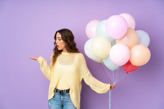 Jonge vrouw die vele ballons over op purpere muur vangen die lege ruimte houden