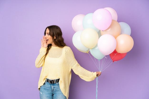Jonge vrouw die vele ballons over op purpere muur vangen die met wijd open mond schreeuwen