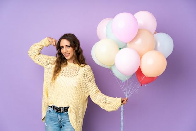 Jonge vrouw die vele ballons over op purpere muur vangen die sterk gebaar maken