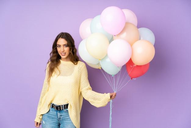 Jonge vrouw die vele ballons over op purpere muur vangen die twijfels en met verwarde gezichtsuitdrukking hebben