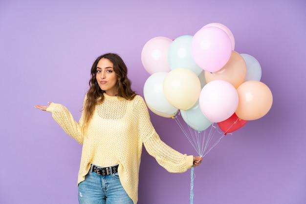 Jonge vrouw die vele ballons over op purpere muur vangen die twijfels met verwarde gezichtsuitdrukking hebben