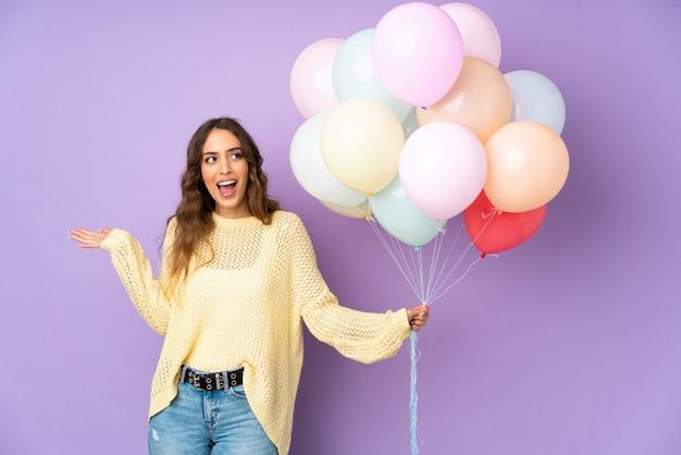 Jonge vrouw die vele ballons over op purpere muur vangen met verraste gelaatsuitdrukking