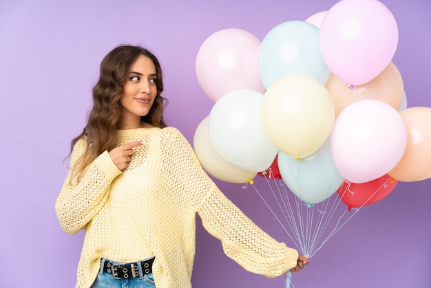 Jonge vrouw die vele ballons over op purpere muur vangt