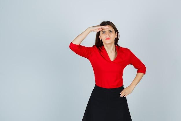Jonge vrouw die ver weg met hand boven het hoofd kijkt, hand op heup in rode blouse houdt