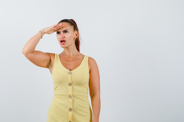 Jonge vrouw die ver weg met hand over hoofd in gele kleding kijkt en gefrustreerd kijkt. vooraanzicht.