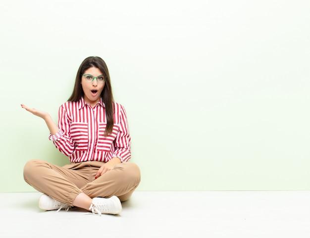 Jonge vrouw die verbaasd en geschokt kijkt, met open mond een voorwerp vasthoudt aan de zijkant op de grond