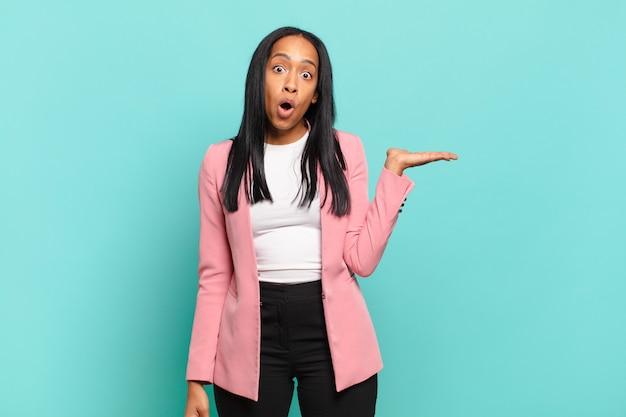 Jonge vrouw die verbaasd en geschokt kijkt, met open mond naar beneden terwijl ze een voorwerp vasthoudt met een open hand op de zijkant