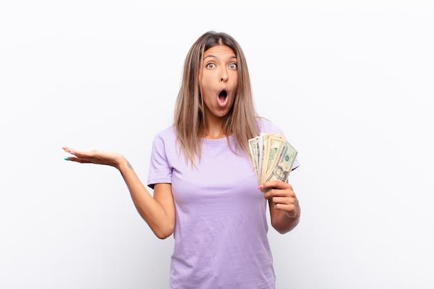 Jonge vrouw die verbaasd en verward kijkt, lip bijt met een nerveus gebaar, het antwoord op het probleem met bankbiljetten niet weet