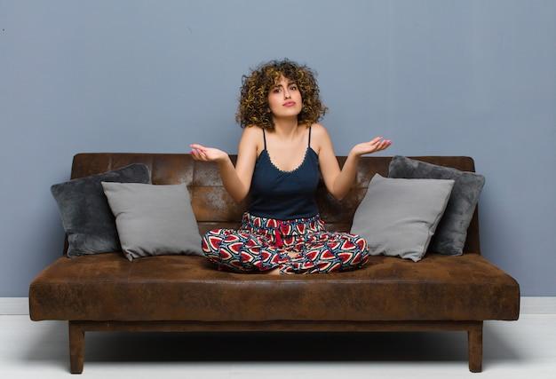 Jonge vrouw die verbaasd, verward en gestrest kijkt, zich afvraagt tussen verschillende opties, zich onzeker voelt terwijl ze op een bank zit.