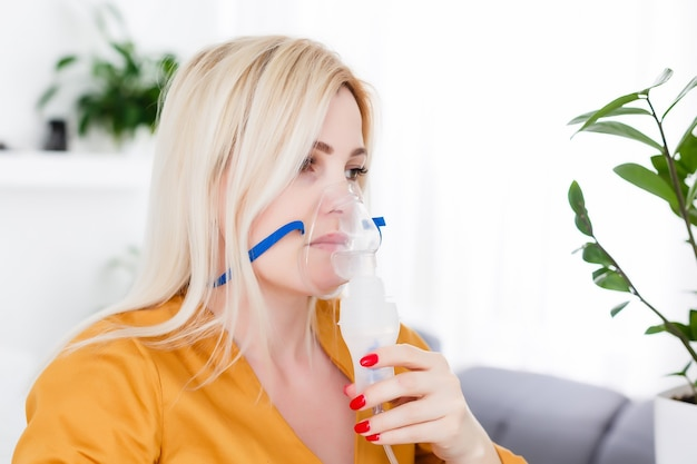 Jonge vrouw die vernevelaar thuis gebruikt voor astma en luchtwegaandoeningen