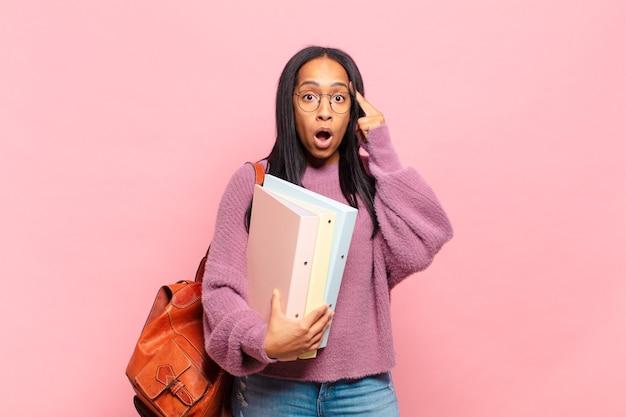 Jonge vrouw die verrast, met open mond, geschokt kijkt en een nieuwe gedachte, idee of concept realiseert