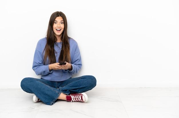 Jonge vrouw die verrast op de grond zit en een bericht stuurt