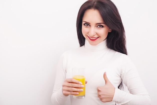 Jonge vrouw die verse jus d'orange drinkt