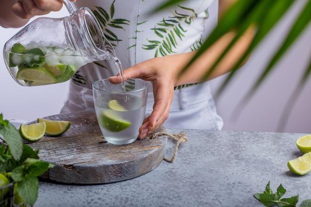 Jonge vrouw die verse limonade van kruik giet in glas