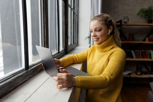 Jonge vrouw die videogesprek op laptop computer thuis heeft
