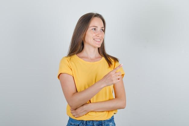 Jonge vrouw die vinger aan kant richt en in t-shirt glimlacht
