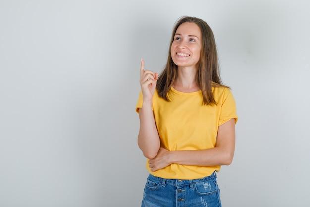 Jonge vrouw die vinger omhoog wijst en in t-shirt glimlacht