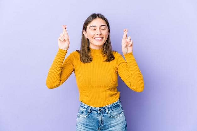 Jonge vrouw die vingers kruist om geluk te hebben
