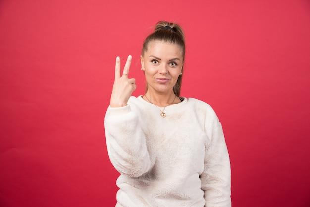 Jonge vrouw die vingers toont die overwinningsteken doen