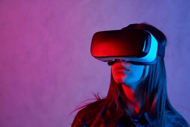 Jonge vrouw die virtuele werkelijkheidshelm gebruikt terwijl het dragen van een jasje