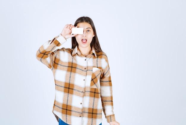 Jonge vrouw die visitekaartje op witte muur toont.