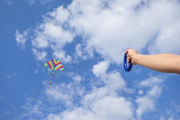 Jonge vrouw die vlieger vliegt in de blauwe lucht