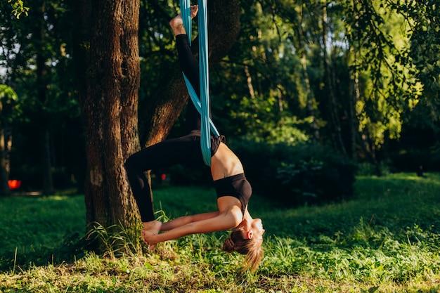 Jonge vrouw die vliegyoga uitoefent bij de boom