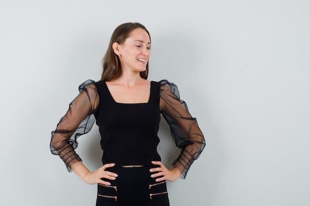 Jonge vrouw die vloer bekijkt terwijl handen op taille in zwarte blouse wordt gehouden en tevreden kijkt