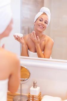 Jonge vrouw die vochtinbrengende crème op gezicht toepast na de douche
