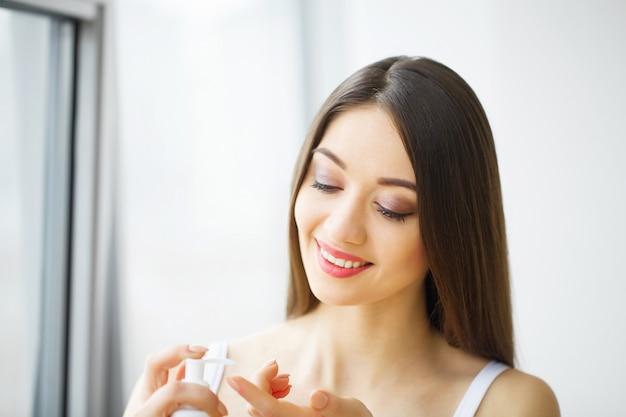 Jonge vrouw die vochtinbrengende crème toepast