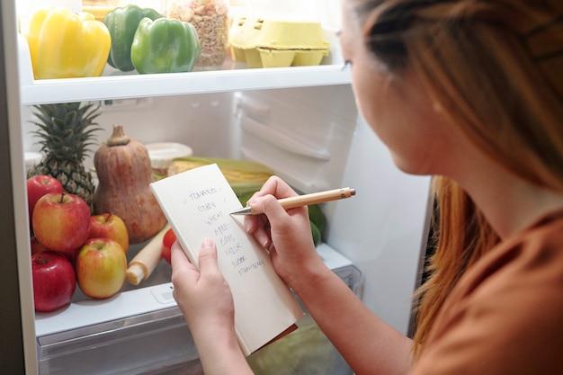 Jonge vrouw die voor een geopende koelkast staat en controleert of ze alles van het boodschappenlijstje heeft gekocht