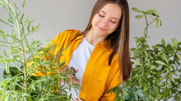 Jonge vrouw die voor groene installaties zorgt
