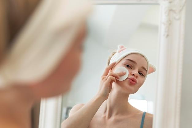 Jonge vrouw die voor haar gezicht zorgt