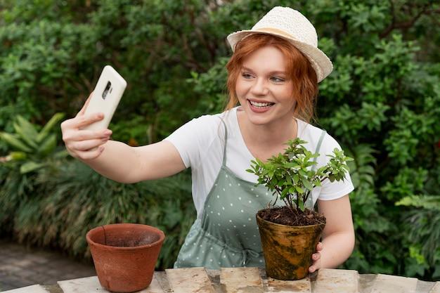 Jonge vrouw die voor haar planten zorgt