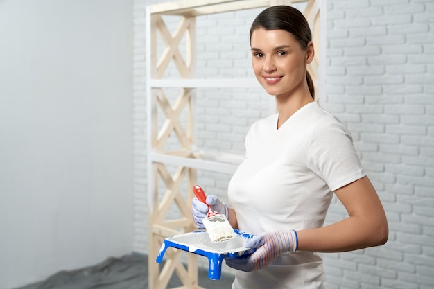 Jonge vrouw die voor het schilderen van rek voorbereidingen treft