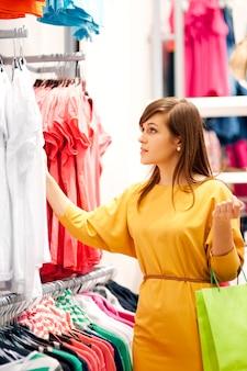 Jonge vrouw die voor kleren winkelt
