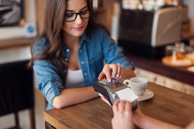Jonge vrouw die voor koffie betaalt door creditcardlezer