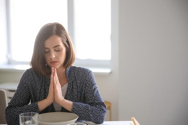 Jonge vrouw die vóór maaltijd thuis bidt