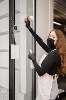 Jonge vrouw die vóór opening desinfecteert