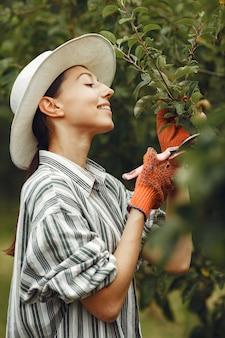 Jonge vrouw die voor planten zorgt. brunette in een hoed en handschoenen. vrouw gebruikt aveeuncator.